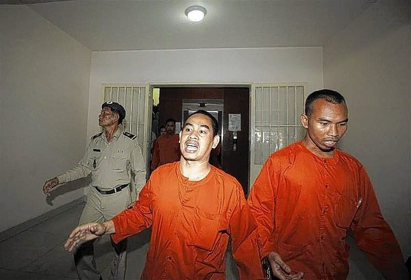 People convicted of plotting to overthrow the Cambodian government walk out after being sentenced at the Phnom Penh Municipal Court April 11, 2014. REUTERS/Samrang Pring