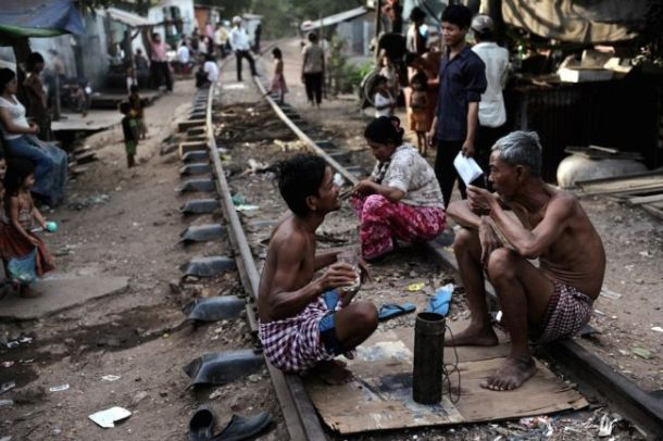 Cambodians sitting along railroad tracks outside their shanty homes in the Boeng Kak slum area of Phnom Penh in 2009. (NICOLAS ASFOURI/AFP/Getty Images)