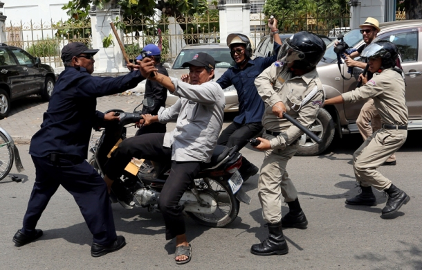 Daun Penh district security guards attack a man on his motorcycle on Street 51 in Phnom Penh shortly after opposition leaders Sam Rainsy and Kem Sokha departed from the area during their International Labor Day march through the city on Thursday. (Siv Channa)