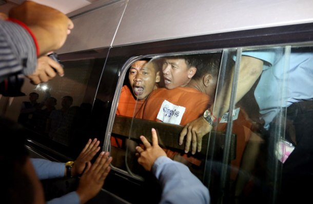 Vorn Pao, center, president of the Independent Democracy of Informal Economy Association, yells to journalists as he and other defendants are driven away from the Phnom Penh Municipal Court on Friday. He and 22 others were tried for their roles in garment strikes that turned violent in January. (Siv Channa)